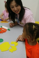 Miss Tracy teaching a 12-36mos old girl animals in Mandarin through Play-doh